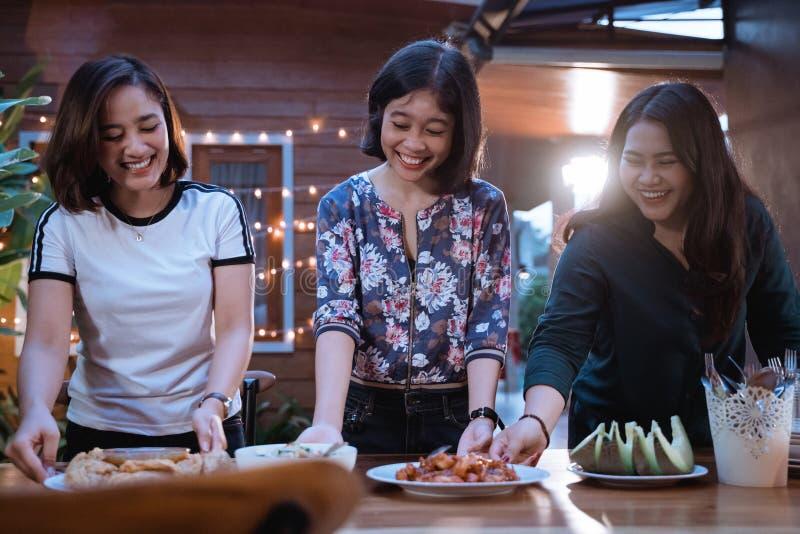 Femme trois préparant la table pour le dîner à l'arrière-cour photographie stock