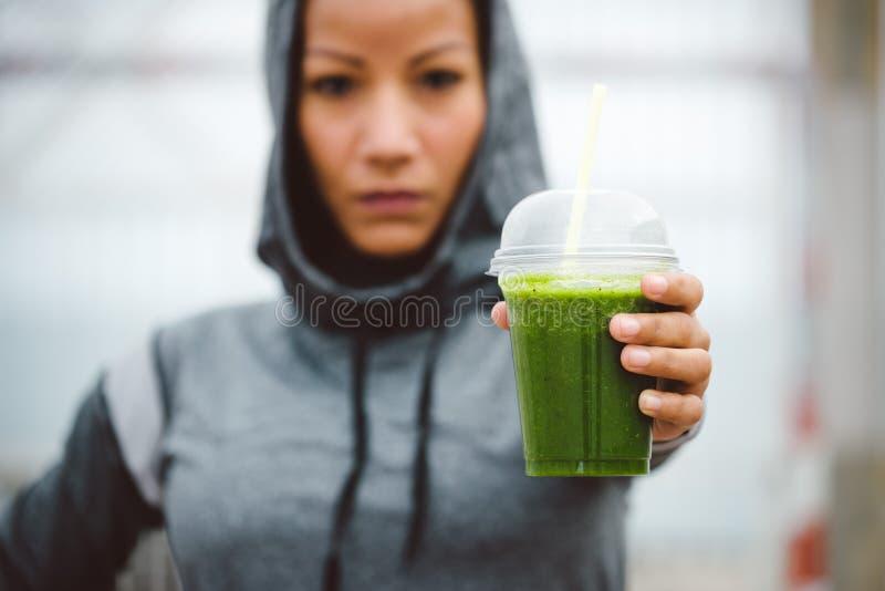 Femme urbaine de forme physique montrant la tasse de smoothie de detox sur le repos de séance d'entraînement images libres de droits
