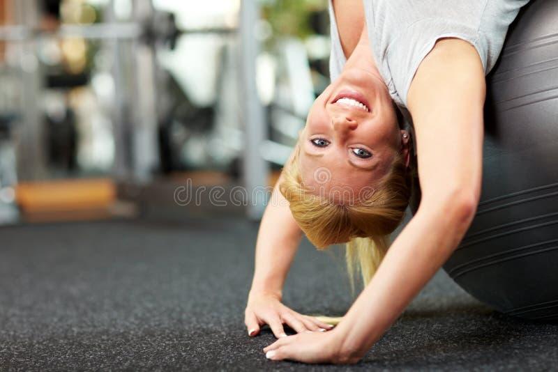 Femme utilisant la bille de gymnastique image stock