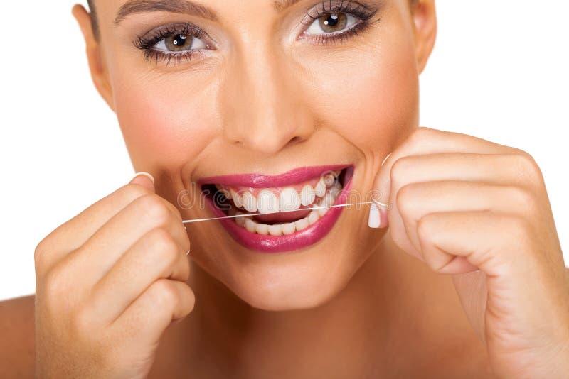 Femme utilisant la soie dentaire images libres de droits