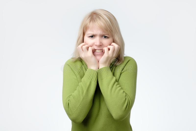 Femme utilisant le chandail vert effrayé, effrayé et soucieux mordant ses ongles de doigt, regardant la caméra image stock