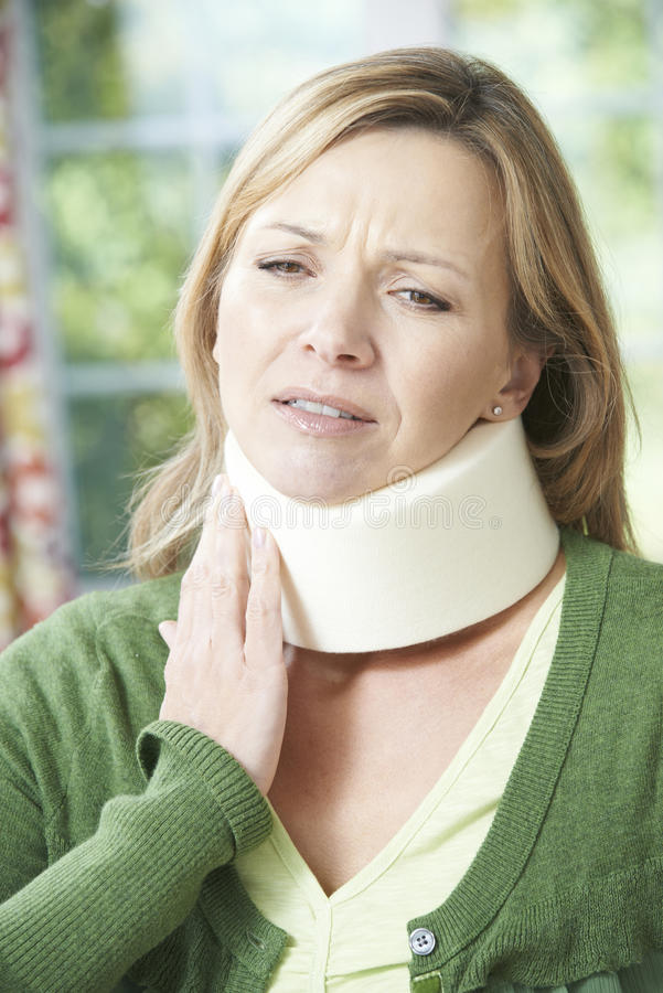 Femme utilisant le collier chirurgical en douleur images libres de droits