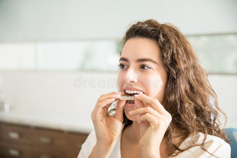 Femme utilisant le dispositif d'alignement clair dans la clinique dentaire photographie stock