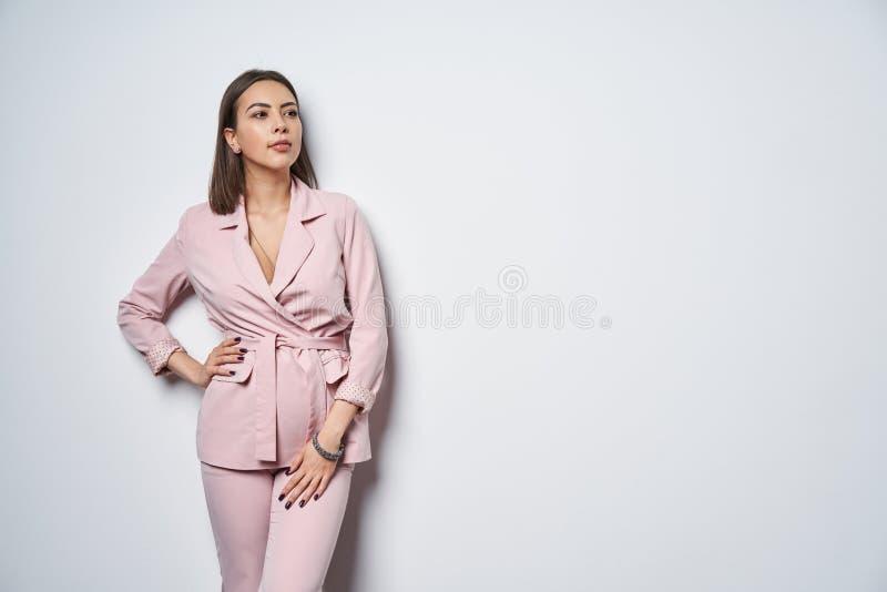 Femme utilisant le mur blanc se tenant prêt de costume rose image stock