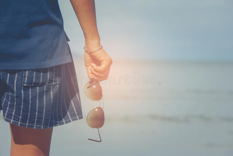 Femme utilisant le pantalon court et le T-shirt se tenant sur la plage de sable et tenant des lunettes de soleil dans le sien mai images stock