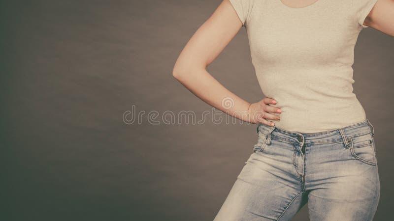 Femme utilisant les jeans minces serrés et le T-shirt blanc image libre de droits