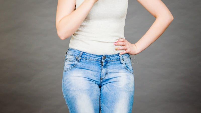 Femme utilisant les jeans minces serrés et le T-shirt blanc photographie stock libre de droits