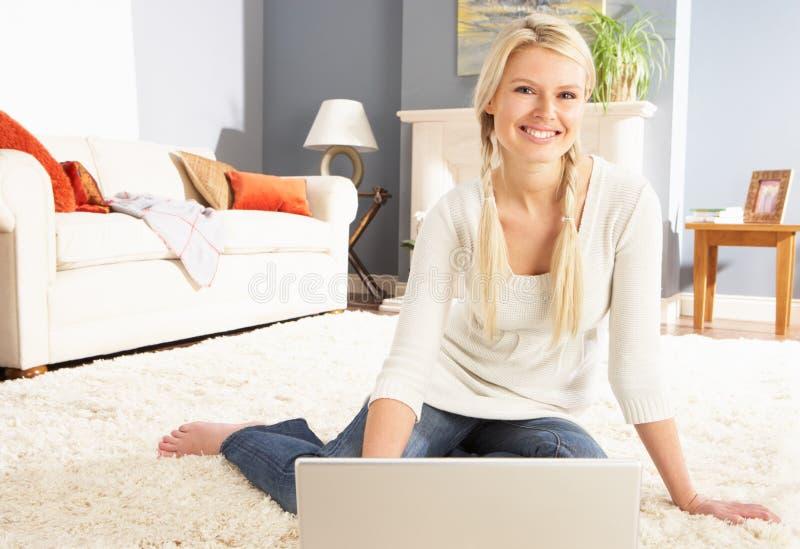 Femme utilisant se reposer de détente d'ordinateur portatif sur la couverture à la maison image libre de droits