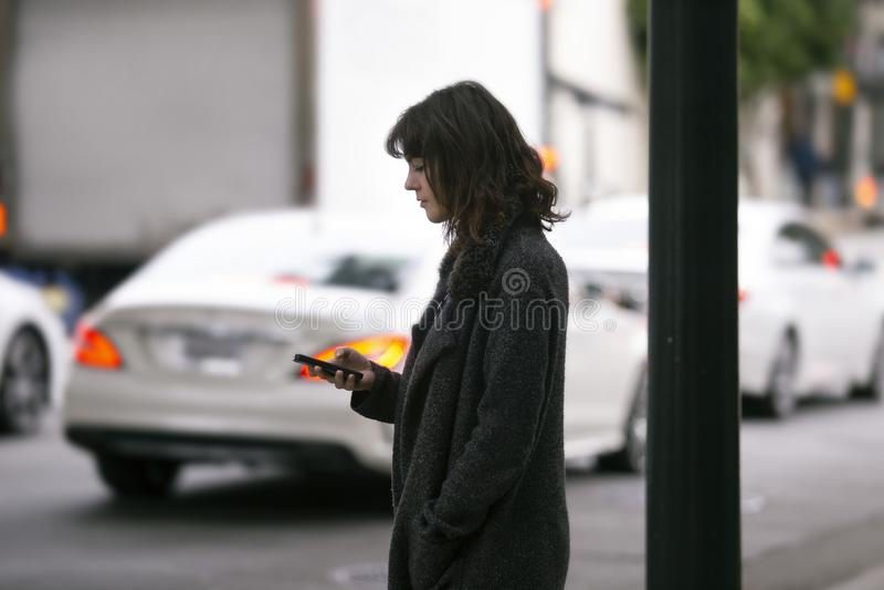 Femme utilisant un appli de Smartphone attendant un Rideshare photographie stock
