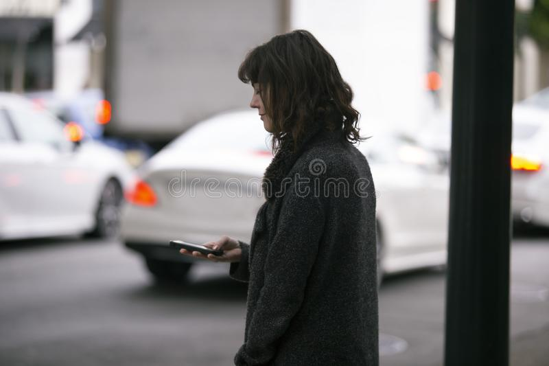 Femme utilisant un appli de Smartphone attendant un Rideshare images stock