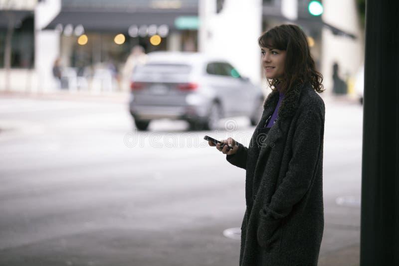 Femme utilisant un appli de Smartphone attendant un Rideshare photos libres de droits
