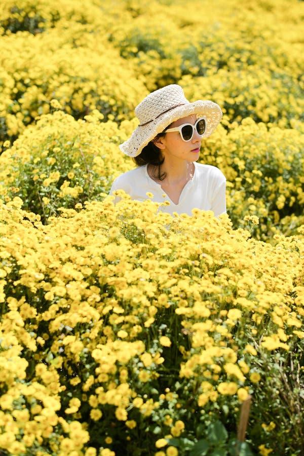 Femme utilisant un chapeau avec les fleurs jaunes images stock
