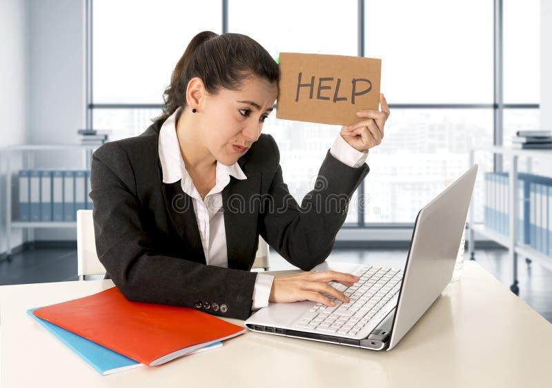 Femme utilisant un costume travaillant sur son ordinateur portable tenant un signe d'aide se reposant au bureau moderne photos libres de droits