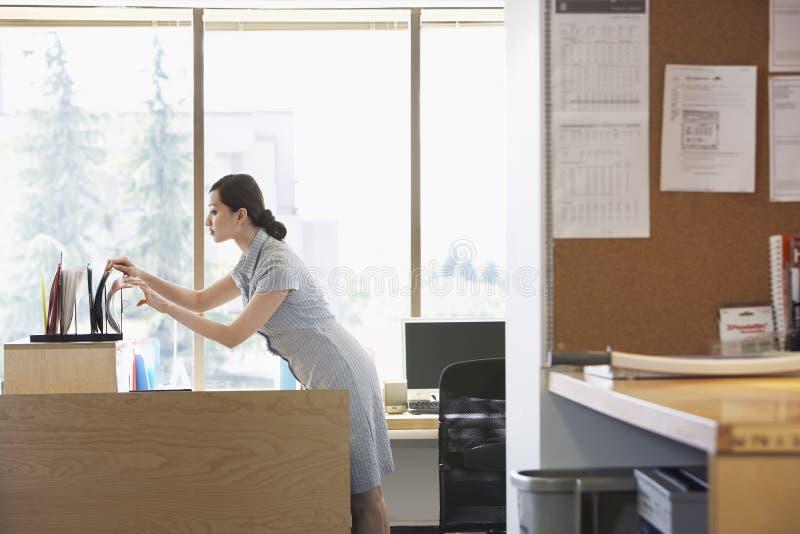 Femme vérifiant des dossiers dans le bureau image libre de droits