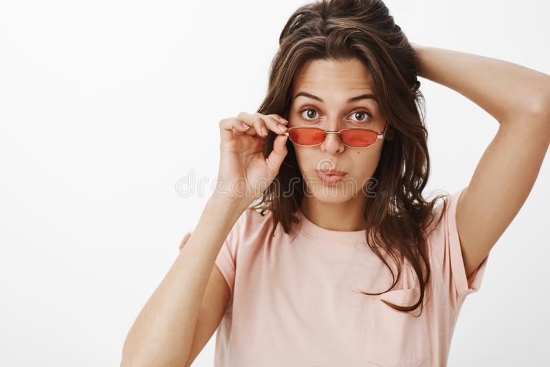 Femme vérifiant l'équipement impressionnant avec le regard fixe de approbation enlevant les lunettes de soleil rouges pliant des  image stock