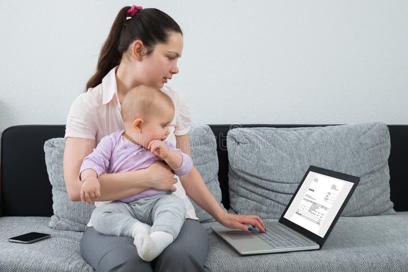 Femme vérifiant la facture sur l'ordinateur portable photos stock