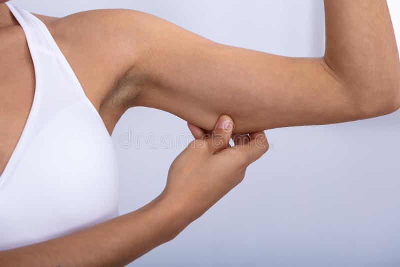 Femme v?rifiant la graisse excessive sur ses bras images stock