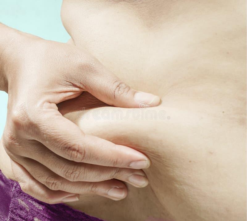 Femme vérifiant la graisse sur son abdomen photographie stock libre de droits