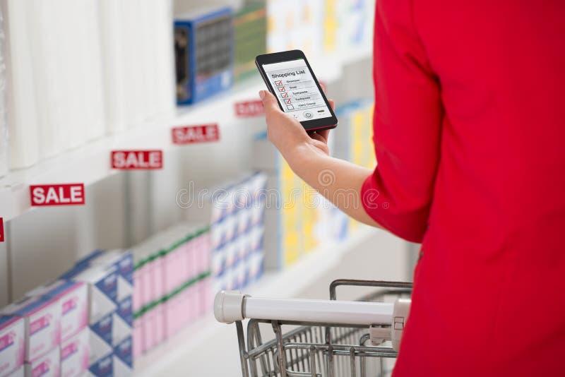 Femme vérifiant la liste d'achats sur Smartphone dans le supermarché images stock