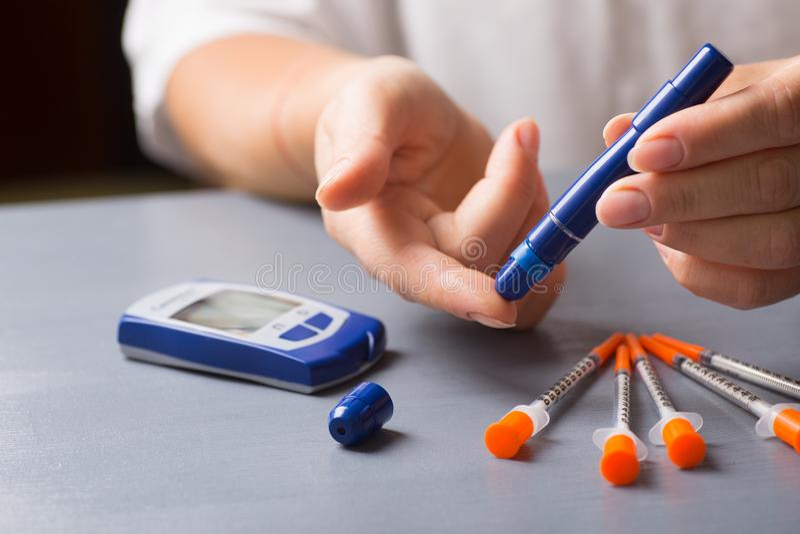 Femme vérifiant le niveau de glucose sanguin utilisant le stylo de seringue avec le glucometer à la maison photo libre de droits