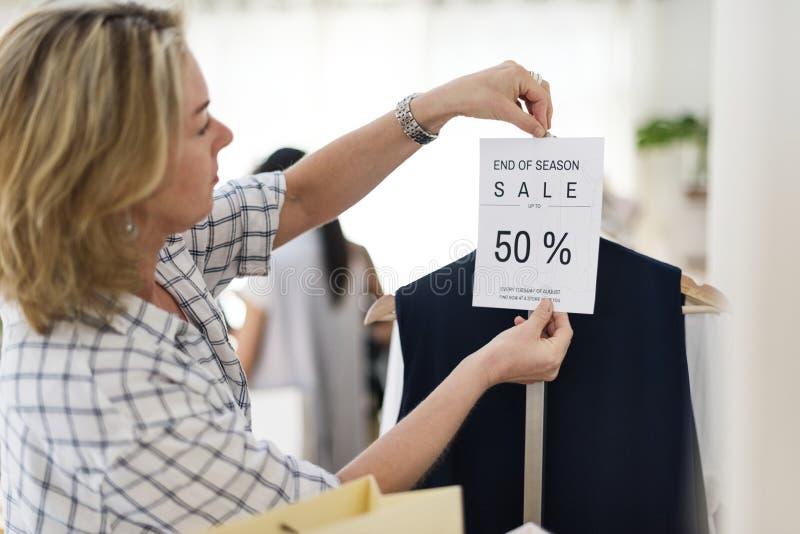 Femme vérifiant les vêtements escomptés images libres de droits