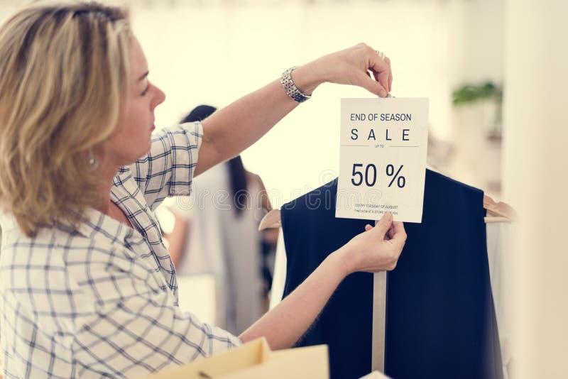Femme vérifiant les vêtements escomptés photographie stock