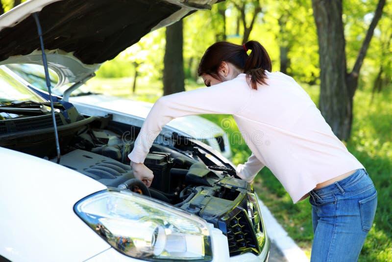 Femme vérifiant son moteur de voiture photographie stock libre de droits