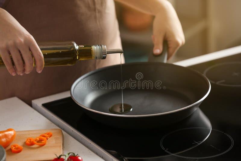 Femme versant l'huile d'olive sur la poêle sur le fourneau photo libre de droits