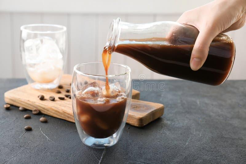 Femme versant le café froid de brew dans le verre images stock