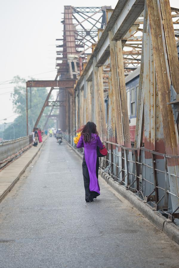 Femme vietnamienne dans la robe traditionnelle ao Dai marchant sur le vieux long pont de Bien, ville de Hanoï photo stock