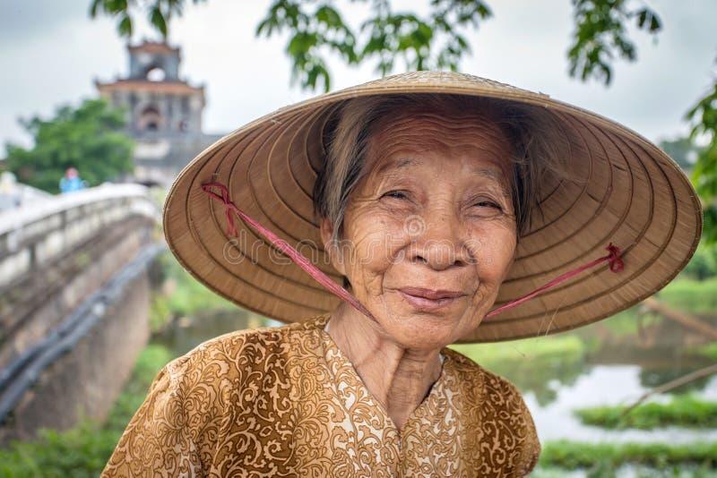 Femme vietnamienne non identifiée utilisant le chapeau conique traditionnel photographie stock libre de droits