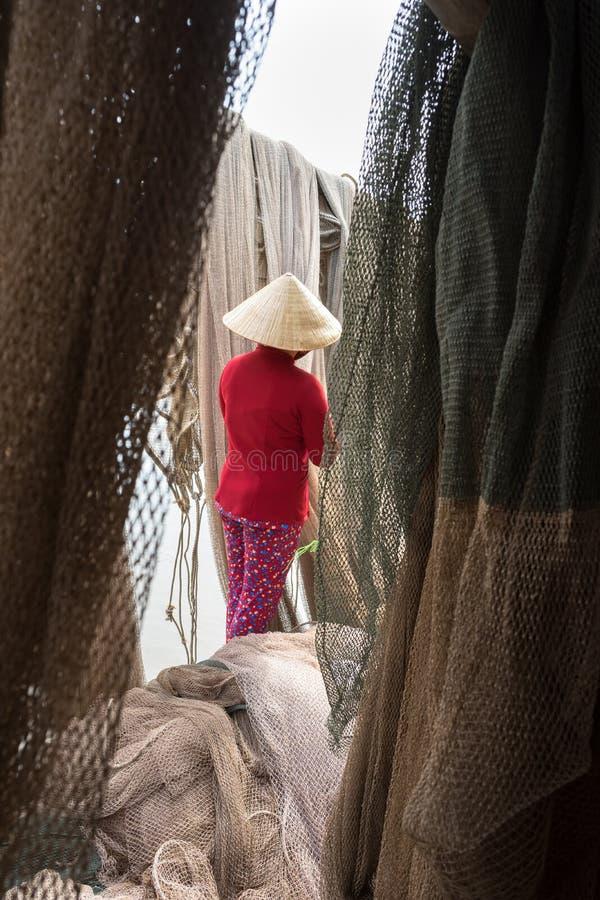 Femme vietnamienne réparant l'épervier de poissons delta dans Ca Mau, le Mékong, Vietnam du Sud image stock