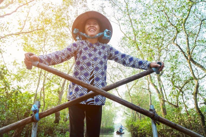 Femme vietnamienne ramant le bateau en bois sur la rivière photo libre de droits