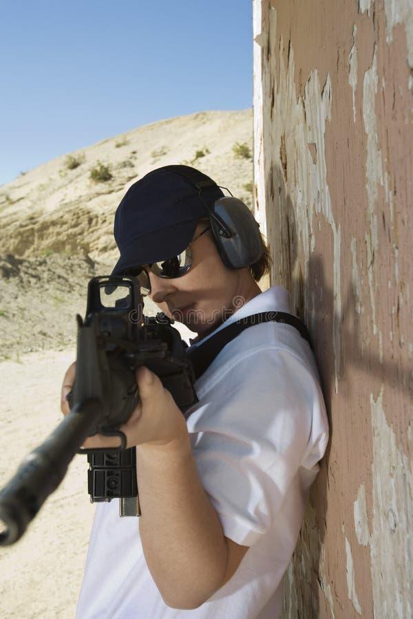 Femme visant la mitrailleuse la chaîne de mise à feu photos libres de droits