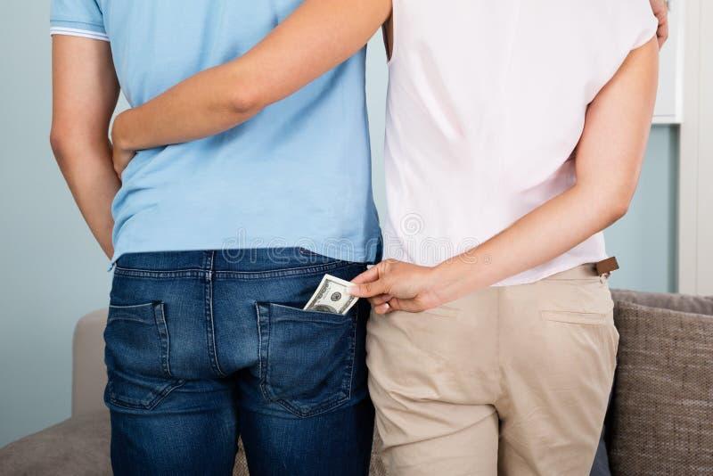 Femme volant l'argent de la poche du ` s de mari image libre de droits