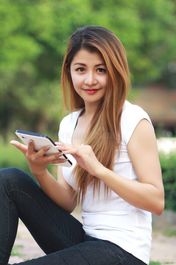 Femmes à l'aide du comprimé numérique en nature photo stock