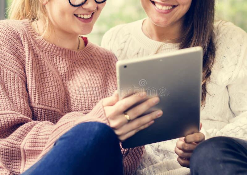 Femmes à l'aide du comprimé numérique ensemble image stock