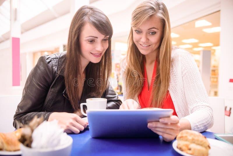 Femmes à l'aide du comprimé numérique tout en ayant le café et des casse-croûte photo libre de droits