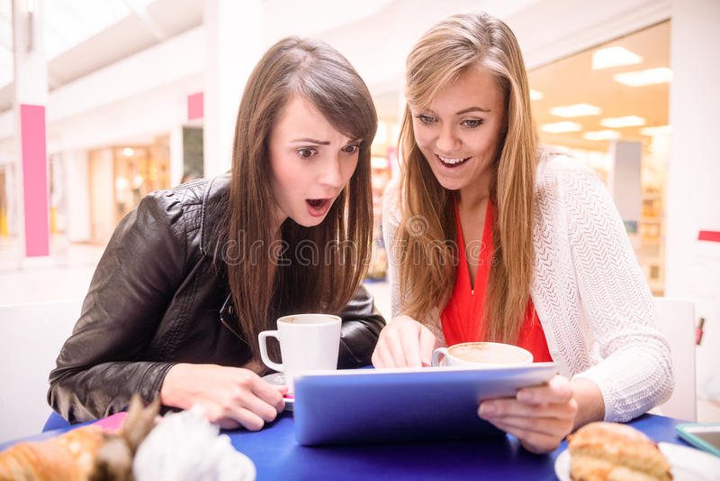 Femmes à l'aide du comprimé numérique tout en ayant le café et des casse-croûte image stock