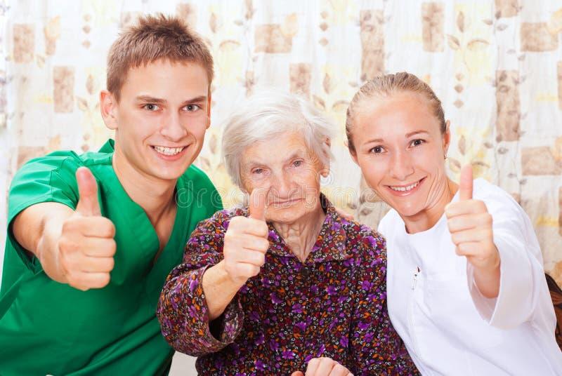 Femme âgée avec les jeunes médecins images libres de droits