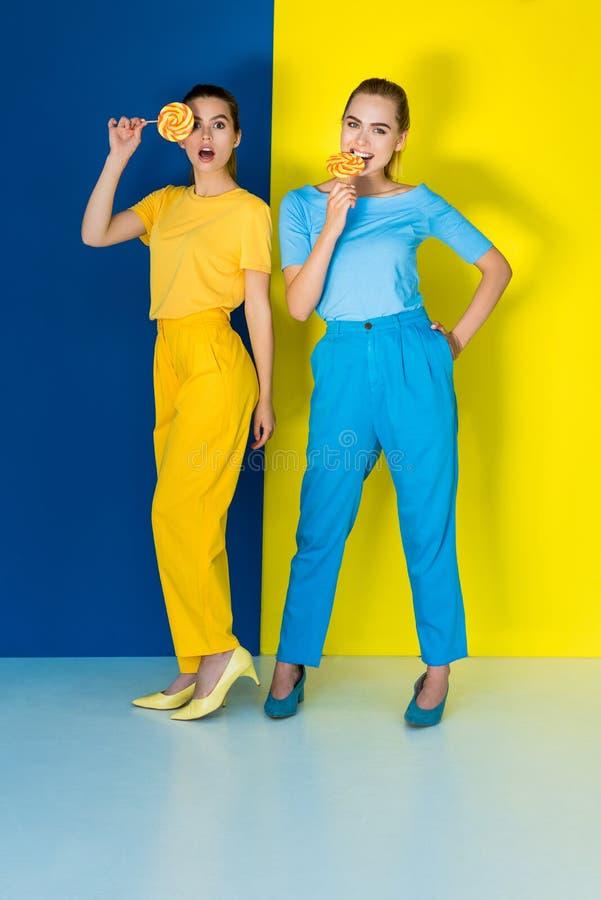 Femmes élégantes élégantes mangeant des lucettes sur le bleu image stock