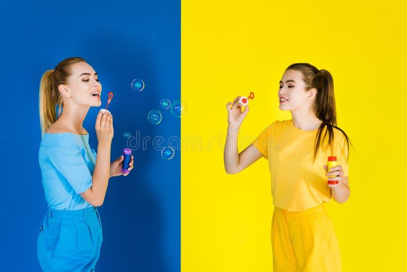 Femmes élégantes élégantes soufflant des bulles sur le bleu photo stock