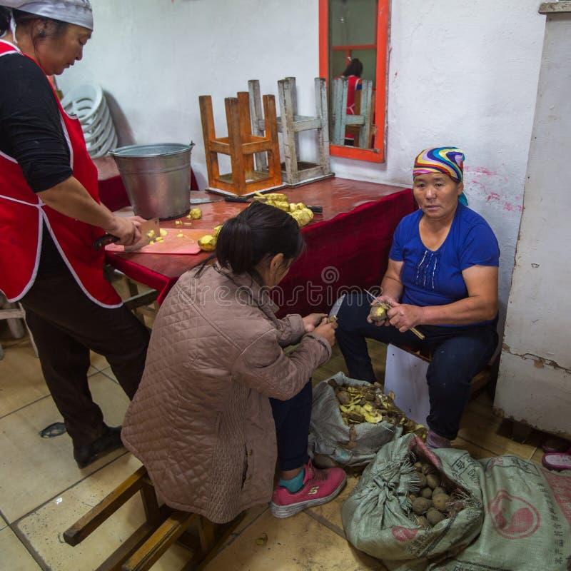 Femmes épluchant des pommes de terre à un restaurant local Dans Bayan-Olgiy la province est peuplée à 88,7% par des Kazakhs photographie stock