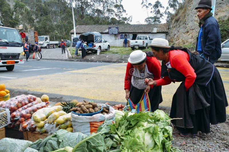 Femmes équatoriennes traditionnellement habillées inspectant des légumes sur un marché images stock
