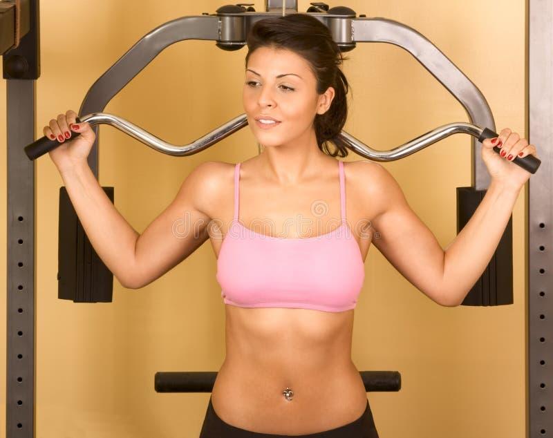 Femmes établissant sur la machine de weight-lifting images stock