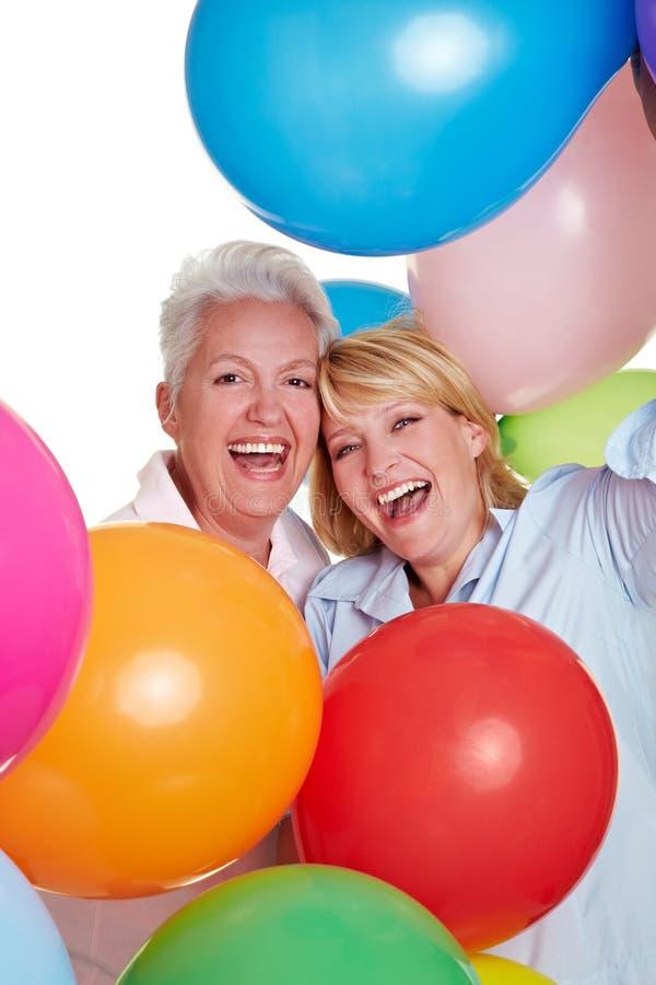 Femmes aînés encourageant avec des ballons image stock
