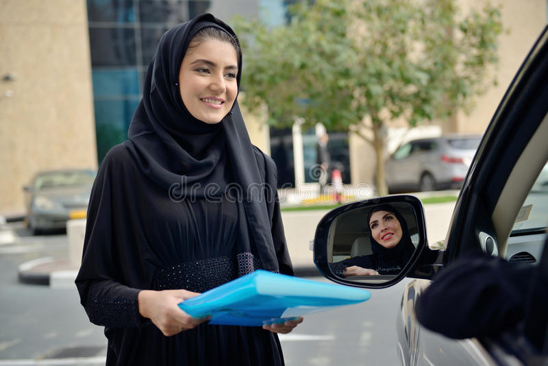 Femmes arabes d'affaires d'Emarati entrant dans la voiture photos libres de droits