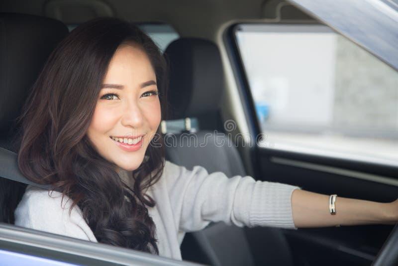 Femmes asiatiques conduisant une voiture et un sourire heureusement avec l'heureuse expression positive pendant la commande pour  photo libre de droits