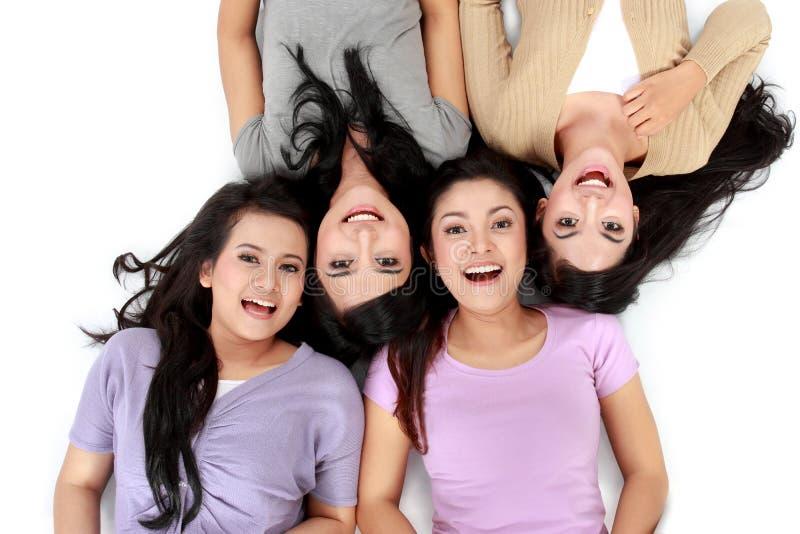 Femmes asiatiques détendant le mensonge de sourire sur l'étage photographie stock libre de droits