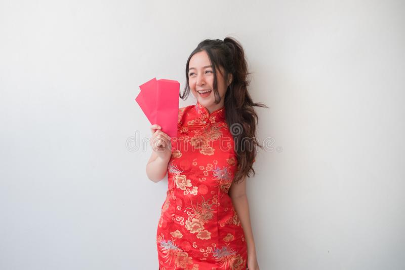 Femmes asiatiques dans des robes et la représentation de cheongsam de chinois traditionnel des enveloppes rouges pendant la nouve images stock